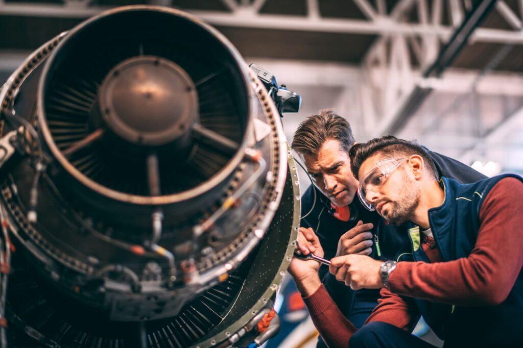 2 engineers working on plane engine